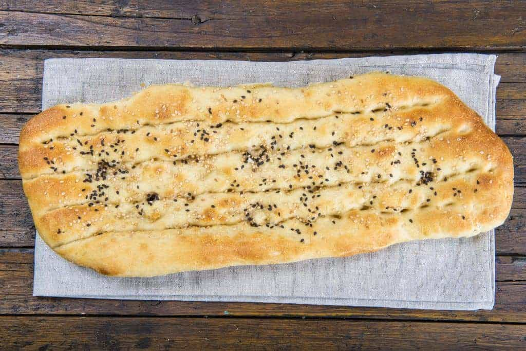 Barbari or Persian bread covered with sesame seeds on the table