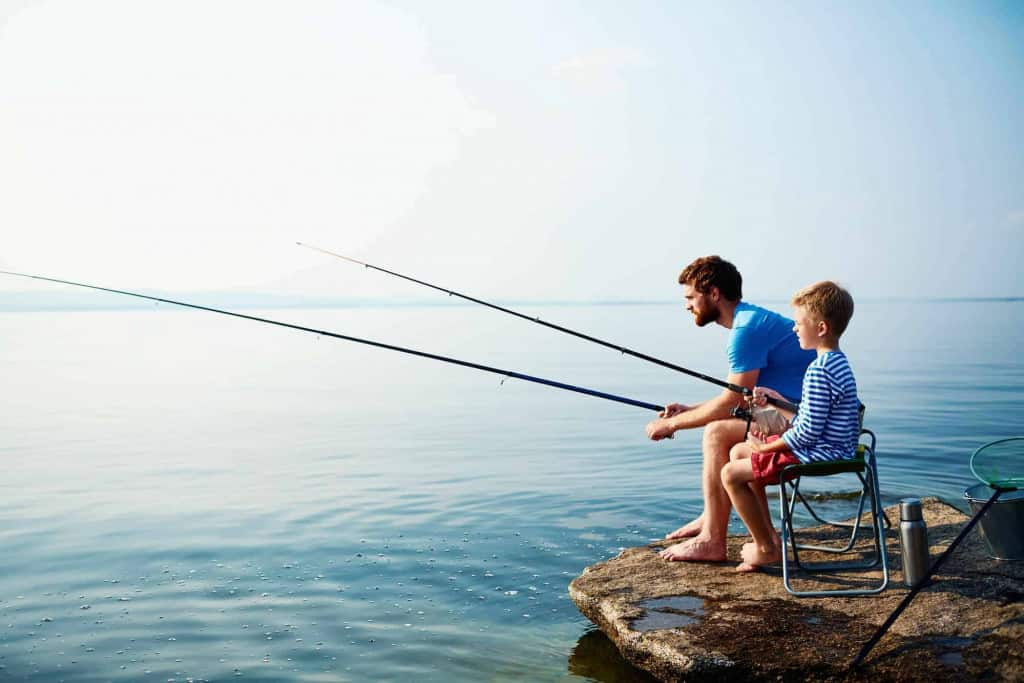 Young man and boy fishing together