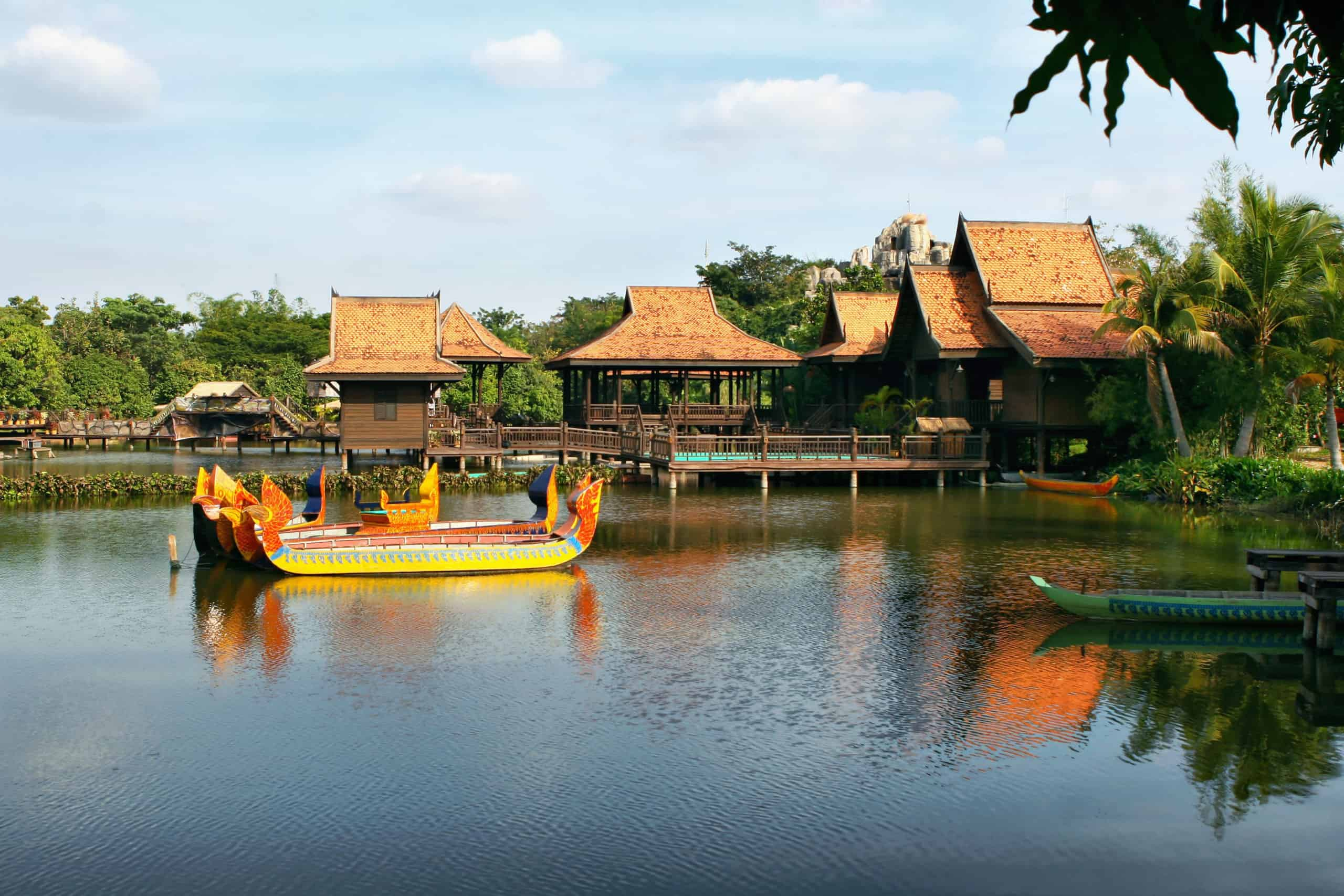 Cultivated park with lake and ancient  boats. Houses on stilts. Hotel in Siem reap. Cambodia.