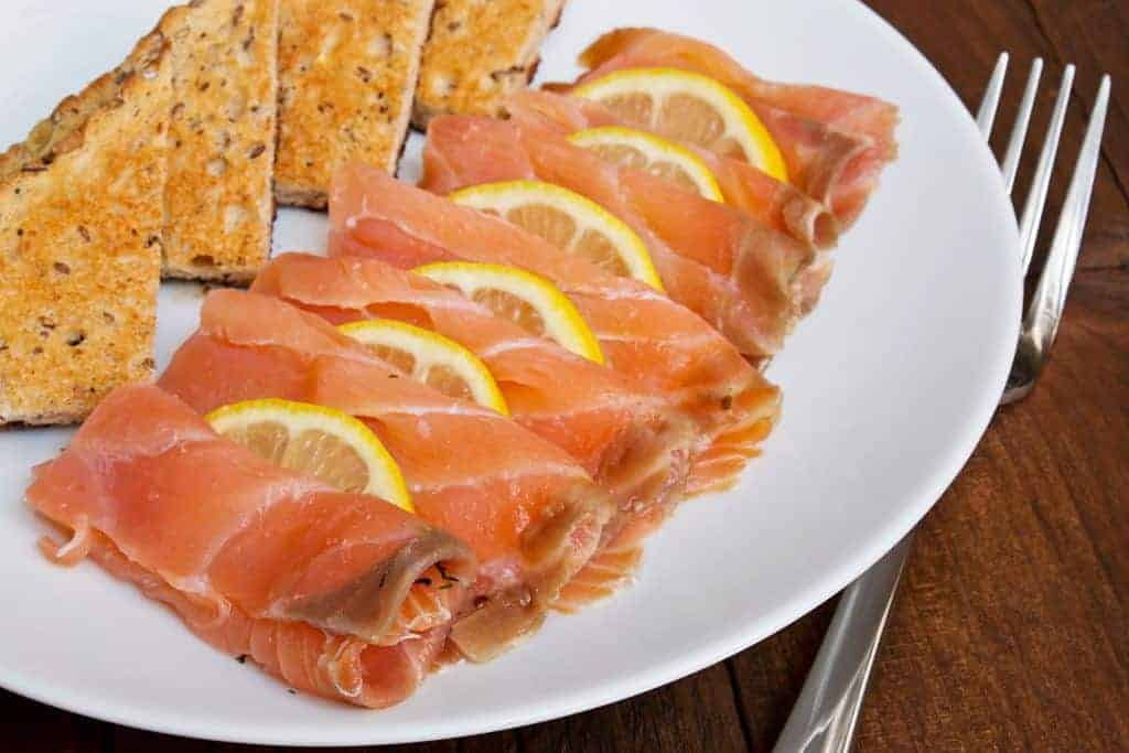 Smoked salmon sliced with lemon slices interleaved and served with traditional toast on a plate in a rustic restaurant table top setting.