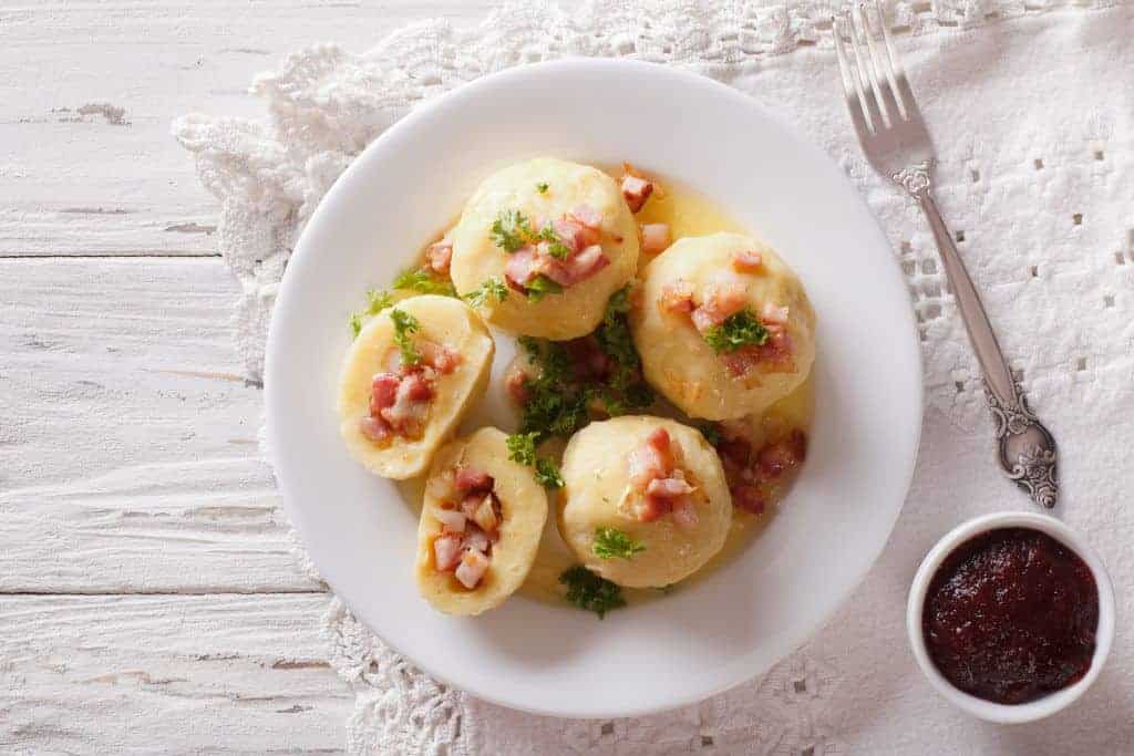 Potato dumplings stuffed with ham, bacon and onion close-up on a plate. Horizontal view from above