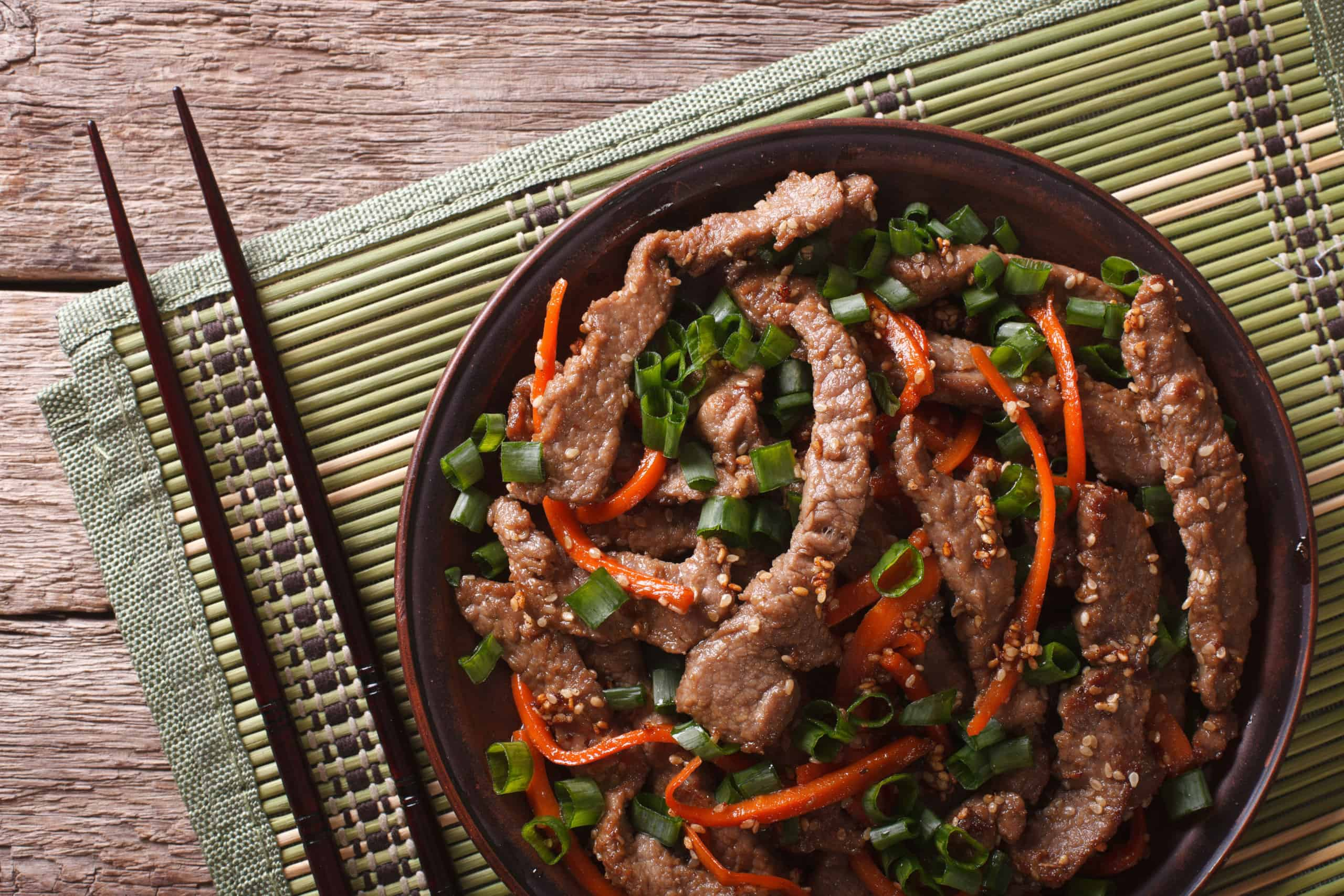 Asian Food: Bulgogi beef slices fried with sesame and carrot close-up on a plate. horizontal top view